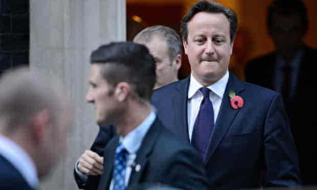 David Cameron, wearing poppy in his lapel and biting his lip, leaves Downing Street