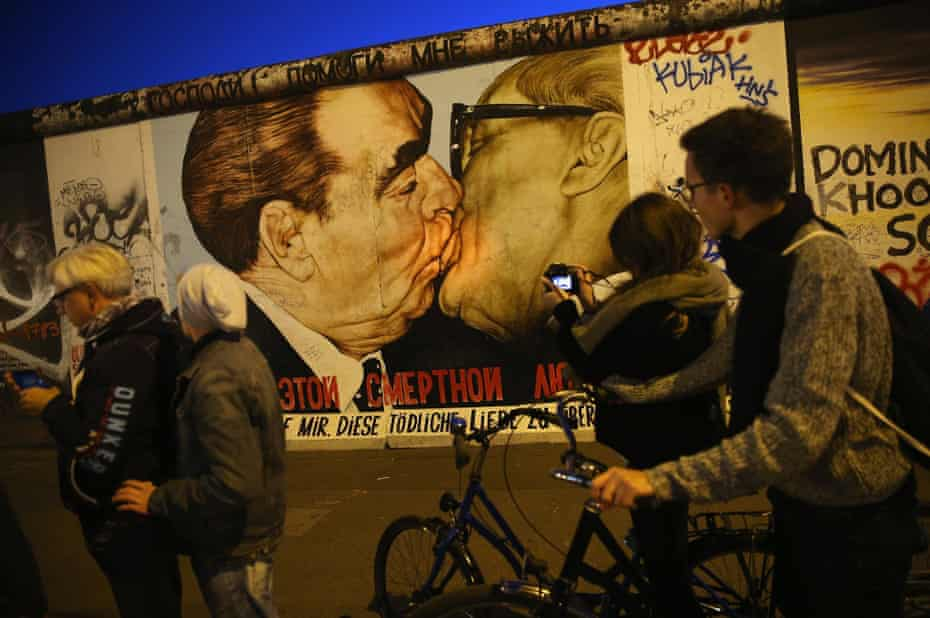 Visitors gather at a mural on the Berlin Wall