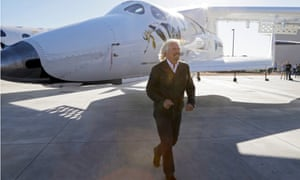 Richard Branson passes a SpaceShipTwo rocket under its mother ship at a Virgin Galactic hangar at Mojave Air and Space Port in Mojave, California.