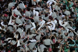 Members of the Castellers de Sants Human Tower team fall after  forming a 'castell' during the XXV human towers, or castells, competetion in Tarragona.