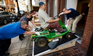 Art handlers push in the Man on a Mower