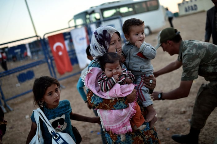 Kurdish refugees evacuate the Syrian town of Ain al-Arab, known as Kobani by the Kurds, at the border crossing on the Turkish-Syrian border