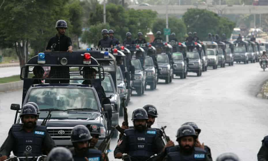 Pakistani police officers patrol the streets of Karachi.
