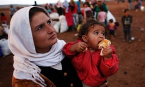 A Syrian Kurdish refugee woman with her daughter wait for transportation after crossing into Turkey.