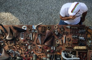 A cyclist looks at old bicycle parts at the local market a day before L'Eroica