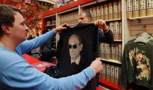 A Russian customer examines a sweatshirt with a printed portrait of Russian President Vladimir Putin in the GUM department store in Moscow, Russia