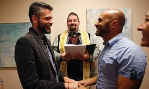 Jim Derrick (L) and Alfie Travassos (R) get married by the Rev Justin Lopez (C) in Salt Lake City.