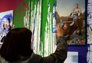 "A visitor takes photos during the ""12 Labors of Putin"" art exhibition marking the 60th birthday of Russia's President Vladimir Putin at the design workshop in Moscow"