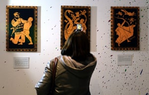 A visitor takes photos of the paintings during the '12 Labours of Putin' art exhibition marking the 60th birthday of Russia's President Vladimir Putin at the design workshop in Moscow