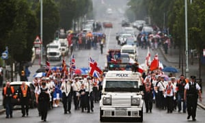 An armoured police vehicle escorts an Orange Order parade on Crumlin Road on 12 July commemorations