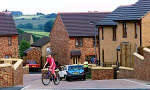 Girl on cycle outside houses