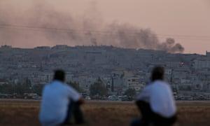 Turkish Kurds on the Turkey-Syria border watch the aftermath of air strikes on Kobani
