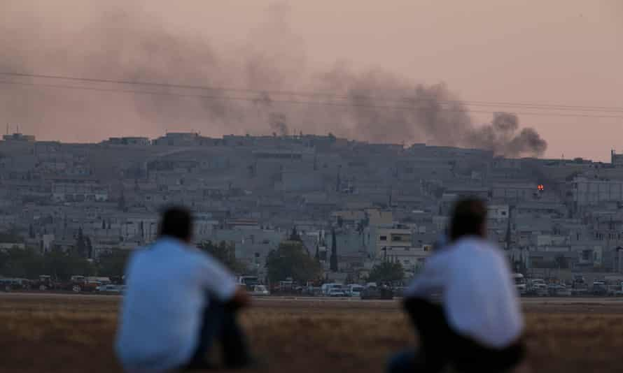 Turkish Kurds on the Turkey-Syria border watch the aftermath of air strikes on Kobani