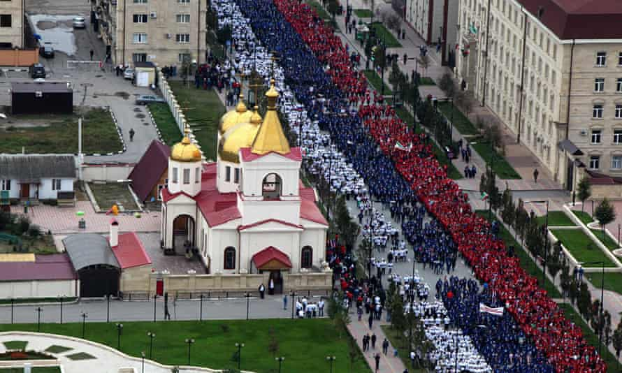 People dressed in colours of the Russian flag march in Chechnya on Vladimir Putin's birthday