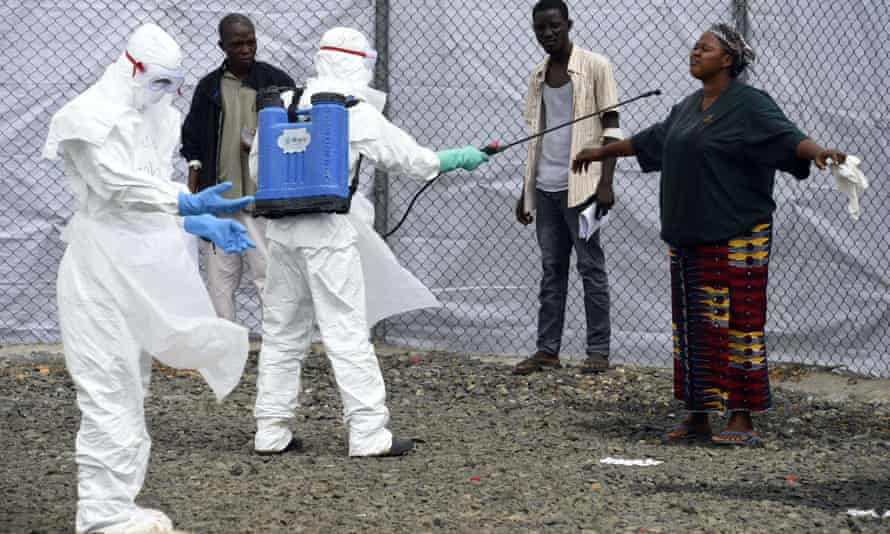 Medical personnel at the Ebola Treatment Centre at Island Hospital in Monrovia disinfect people who have brought in patients suspected of having the Ebola virus.