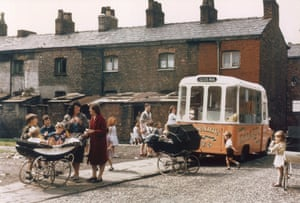 Mothers and young children flock round an ice cream van in a back street in Hulme, Manchester.
