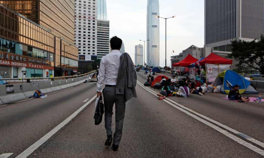 A man walks to work as the pro-democracy student protesters sleep on a roadside in the occupied areas surrounding the government complex in Hong Kong Oct. 6, 2014.