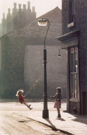 Two young girls swing on a rope attached to a lampost outside a corner shop in Hulme, Manchester in the evening light, 1965.
