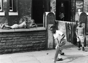 Young boys play cricket in the street in Manchester 1964.