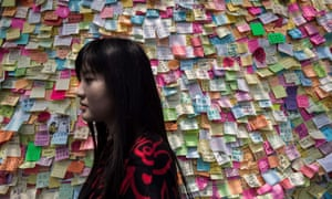 Woman walks past wall of messages
