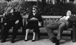 An elderly lady sits stiffly between two snoozing men, 1961.