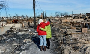 Neighbours embrace among the remains of the many houses that burned down in Breezy Point, New York, in the aftermath of Hurricane Sandy.