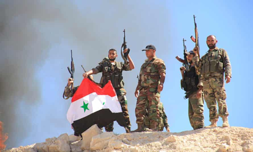 Syrian forces raise the national flag