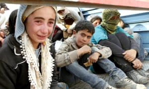 A newly arrived Syrian Kurdish refugee girl cries as she sits in the back of a truck after crossing into Turkey from the Syrian border town of Kobani on October 7, 2014 near the southeastern town of Suruc in Sanliurfa province, Turkey.