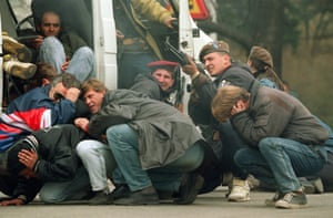 April 6, 1992: A Bosnian paramilitary returns fire in downtown Sarajevo as he and civilians come under fire from Bosnian Serb snipers.