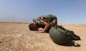 A Kurdish Peshmerga soldier prays on the battlefield.