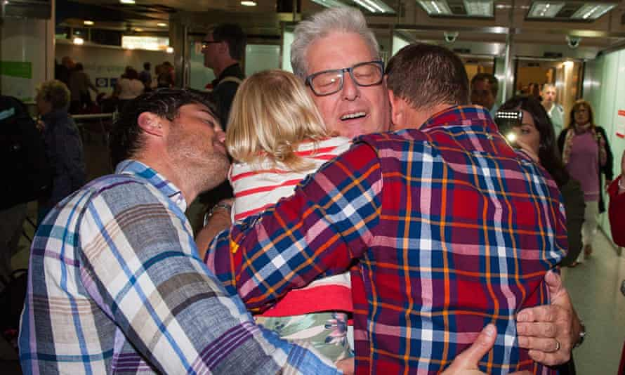 Ray Coles (centre) is greeted by his family at Gatwick airport