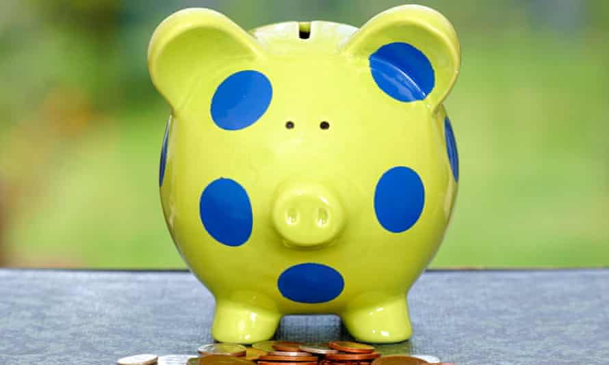 Child's piggy bank with coins piled underneath