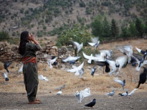 Zilan, a female PJAK guerrilla binds her hair before starting her daily routine inside the camp in Qandil, Kurdistan, 2012.