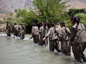 A group of female PJAK guerrillas wade through a river to pass from one side of the Qandil mountains to another.