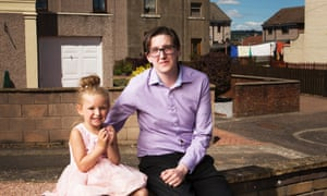 Tommy Inglis sitting on a brick wall with his young niece