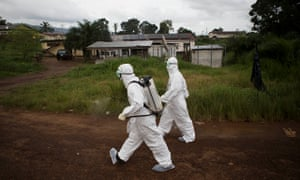 Healthcare workers spray disinfectant to prevent the spread of the Ebola virus in Sierra Leone