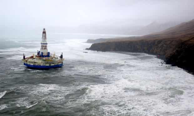 Waves crash over the conical drilling unit Kulluk where it sits aground on the southeast side of Sitkalidak Island Oil Rig Kulluk runs aground, Alaska