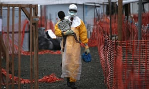 A Doctors Without Borders health worker in protective clothing carries a child suspected of having Ebola in the MSF treatment centre in Paynesville, Liberia.
