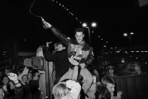 man in crowd waving bottle in air during berlin wall opening
