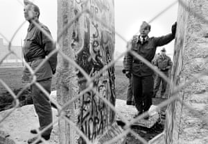 Two soldiers guarding a chunk of wall during fall of the Berlin Wall