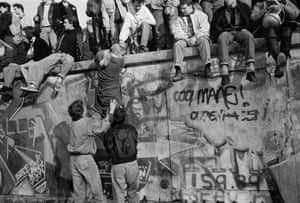 Crowd of people sitting and climbing on the Berlin Wall after opening of border