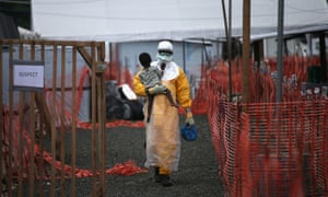 A health worker carries a child suspected of having Ebola into the MSF treatment centre in Paynesville, Liberia.