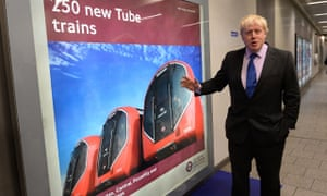 Boris Johnson showing a poster of the New Tube trains