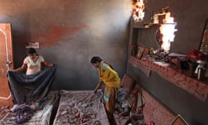 Indian villagers salvage their belongings from one of the houses damaged in shelling by Pakistani tr