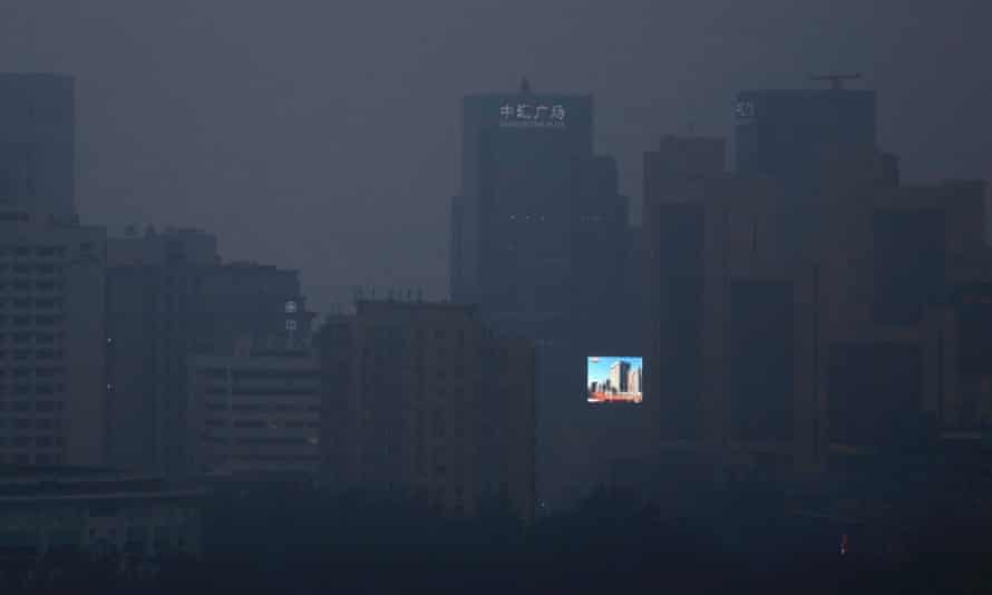 A large screen showing a view of blue skies and buildings is seen amid the smog in Beijing.