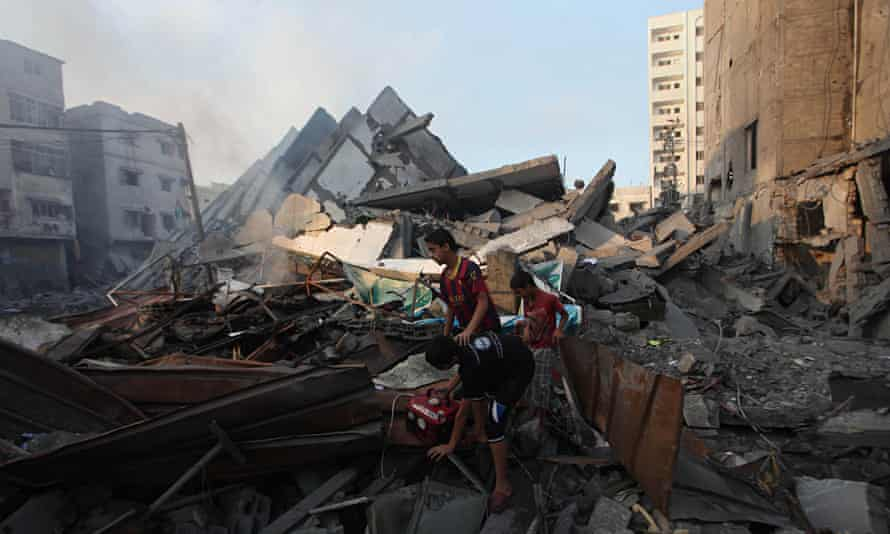 Palestinian children search among the rubble of 15-storey Basha Tower in Gaza.