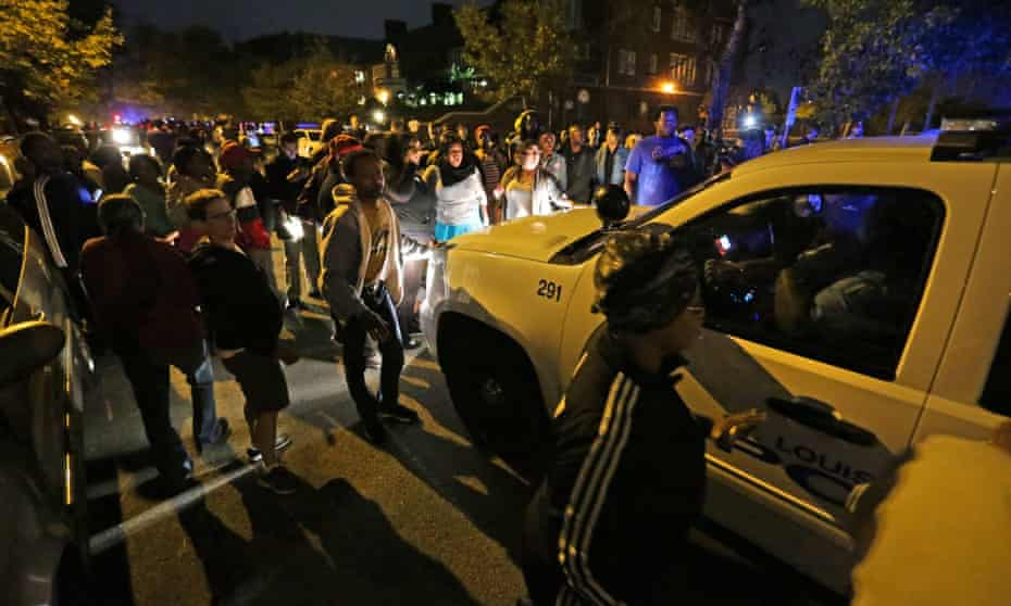 A crowd gathers Wednesday near the scene in south St Louis where a man was fatally shot by an off-duty police officer.