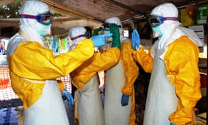 Health workers in Guinea, where the outbreak started, wear protective suits at Donka hospital in Conakry.