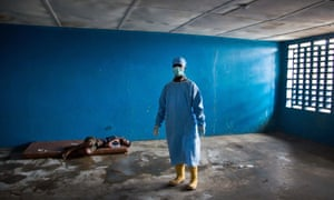A healthcare worker stands next to a woman who has died of Ebola related symptoms in West Point, Monrovia, Liberia.