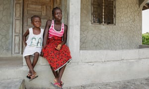 Orphaned Liberians Tina Powell (R) and Dianna Powell (L) sit in front their home after surviving the deadly Ebola virus but loosing both parents and six other relatives to Ebola at the New Dolos Town Community in Margibi County, Liberia, 09 October 2014.